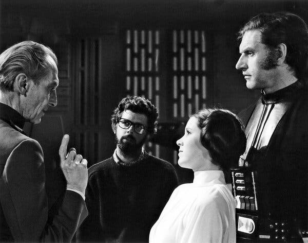 "From left, Peter Cushing, George Lucas, Carrie Fisher and Mr. Prowse on the set of the first ""Star Wars"" movie, which was released in 1977."